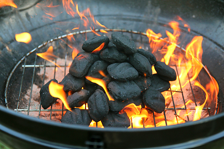 The Coal bricks on a barbeque grill are covered in fire as the charcoal heats up.
