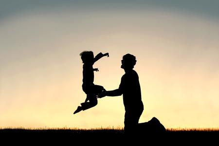 embrace family: Una silueta de un niño feliz niño está saltando a los brazos amorosos de su padre aislados contra la puesta de sol en un día de verano.
