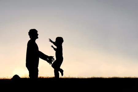 夏の日の夕暮れ時の抱擁を彼の父を迎えるために彼の実行中に笑って幸せな若い子のシルエット。