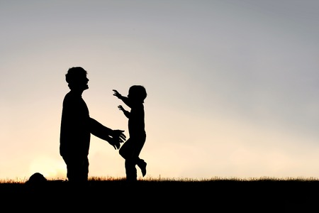 hug: Silhouette of a happy young child smiling as he runs to greet his father with a hug at sunset on a summer day.