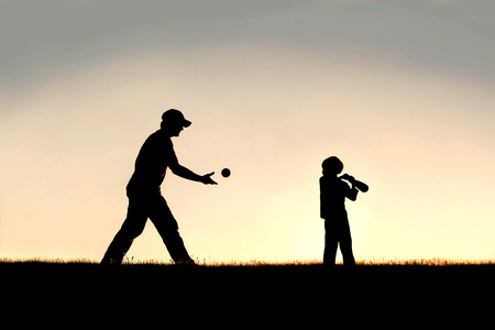 A silhouette of a young father and his little boy child playing baseball outside on a summer evening.