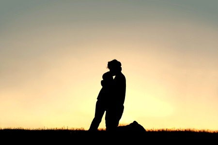 A silhouette of a father lovingly hugging and kissing his young child on the head while isolated against the sunsetting sky on a summer day.