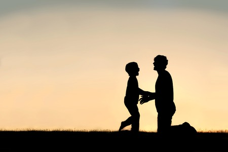 Silhouette of a happy little child greeting his father to hug him outside on a summer day, sihouetted against the sunset in the sky.