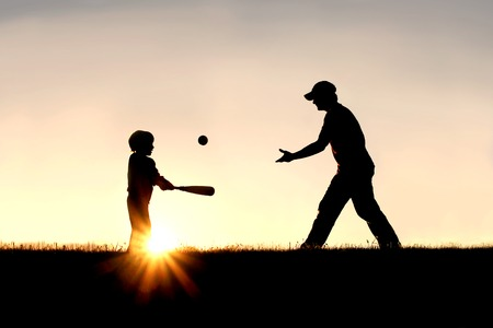 baseball: A silhouette of a father and his young child playing baseball outside, isolated against the sunsetting sky on a summer day.