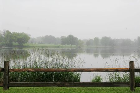 fence: A wooden Split rail fence is framing the bottom of a landscape scene of a lake and trees on a foggy, rainy day.