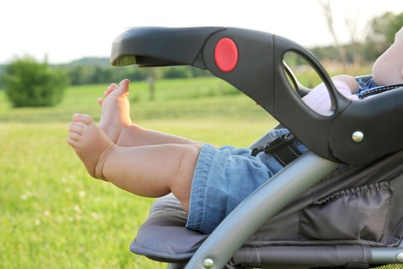 folding chair: The cute, chubby legs of a newborn baby girl are sticking out of a stroller while on a walk outside in the country.