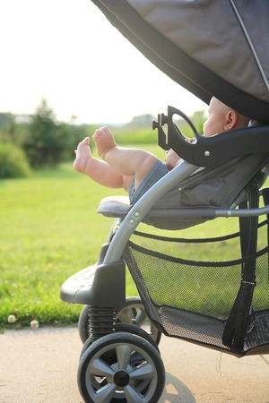 The cute, chubby legs of a newborn baby girl are sticking out of a stroller while on a walk outside in the country.