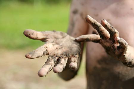 夏の外非常に汚い、ぬかるんだ小さな男の子子供の手にクローズ アップ。