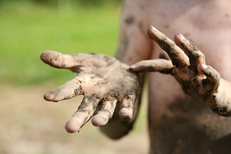 Close up on the hands of a very dirty and muddly little boy child outside in the summer.
