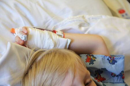 A child is laying on a hospital bed with his arm and hand raised above his head with an I.V. and bandage on it.