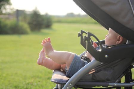 신생아 소녀의 귀엽고 통통한 다리는 동안 나라 밖에서 산책에 유모차의 바깥으로 튀어 나와있다.