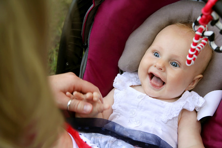 children laughing: A beautiful newborn baby girl is laughing and sticking out her tounge as her mother holds her handswhile she sits in her car seat. Stock Photo