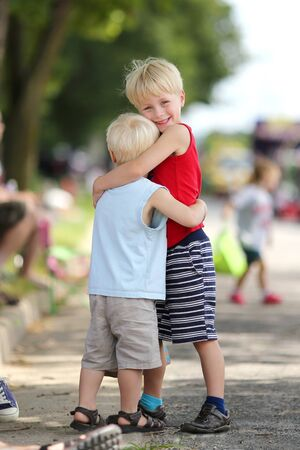 parades: Two happy young children, a boy and his little brother, are standing outside at a small town American parade in the summer.