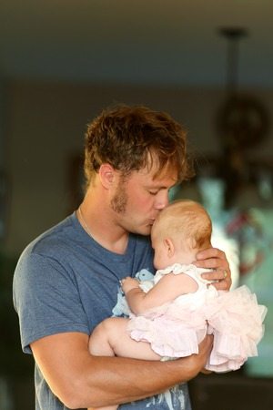 lovingly: A happy young father is lovingly hugginghis baby daughter and kissing her forehead. Stock Photo