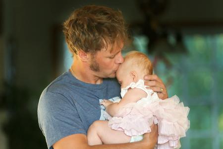 bacio: Un giovane padre felice è hugginghis amorevolmente figlia e baciare la fronte.