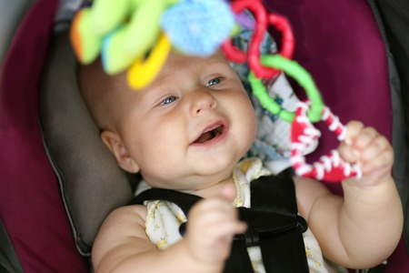 A happy 5 month old baby girl is playing with toys in her car safety seat Imagens