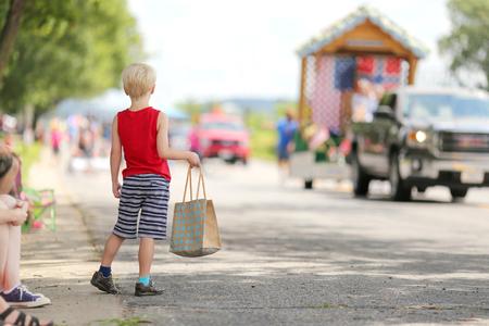 夏季には小さな町のアメリカのパレードを見て、お菓子の袋を持って外に立って若い男の子。 写真素材