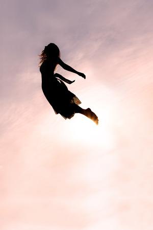 若い女性が先頭を立ち下がりのシルエット夕暮れ時の空を。 写真素材
