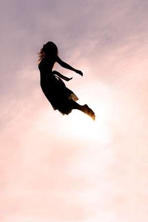 el cielo: Silueta de una mujer joven que cae de cabeza en el cielo al atardecer.
