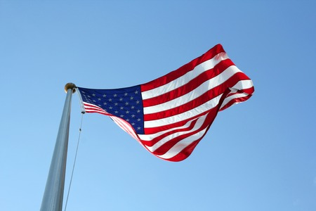 A towering red white and blue American U.S.A. flag is blowing in the wind in front of a blue sky background.