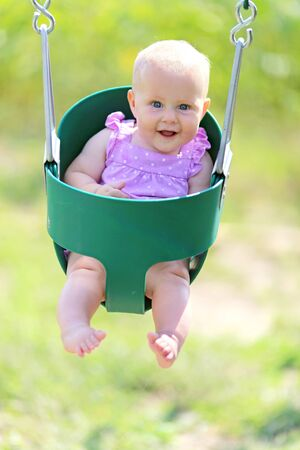 six months: A happy little 6 month old baby girl is smiling as she sits on a swing at a playground.