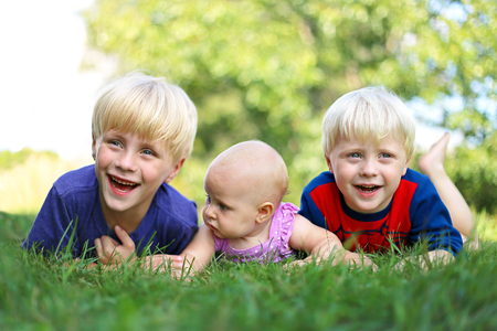 3 6 months: Three happy young siblings: a young child, his little brother and their baby girl sister are laying outside in the grass on a summer day,  laughing.
