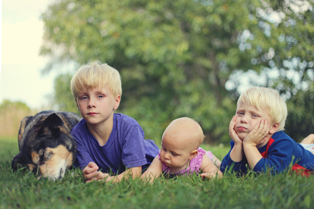 3 6 months: Three young children are bored and hanging out outside in the grass next to their German Shepherd dog on a summer day.  VIntage style color.