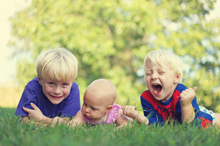 3 6 months: Three silly and happy young siblings: a young child, his little brother and their baby girl sister are laying outside in the grass on a summer day,  laughing.