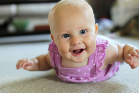 幸せな 6 ヶ月古い赤ん坊少女は自宅に彼女のおなかの上敷設は笑みを浮かべて、クロールましょう。