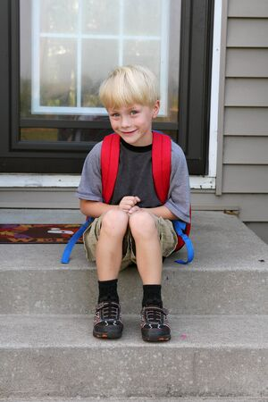 kindergartener: A cute young child is sitting on his front steps of his home wearing his backback on his first day of school.