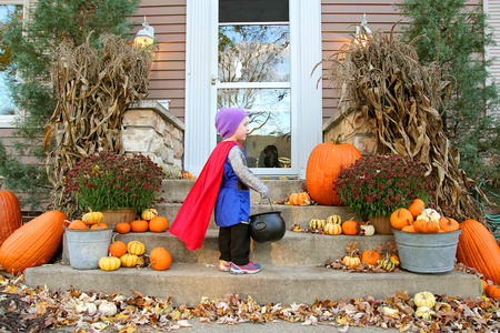 treating: A young child dressed up in a costume like a knight with a cape is standing at a house waiting for candy while trick-or-treating on Halloween.