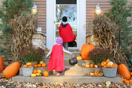 Two young children dressed up in costumes are waiting at a house for candy while Trick-or-Treating on Halloween.