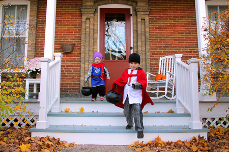 Two young American children dressed in knight costumes are trick-or-treating on Halloween.