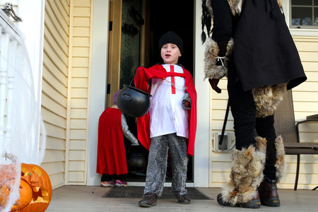 treating: A happy young child dressed up in a knight costume is smiling as he holds up his bag of candy outside a house while trick-or-treating on Halloween. Stock Photo