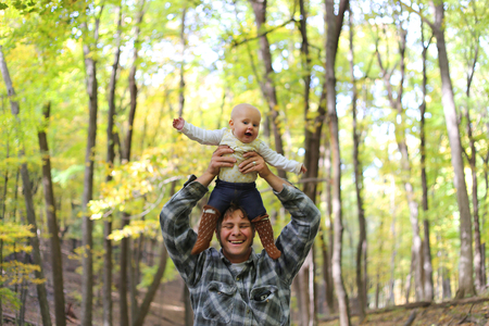 piggy back: A happy young father is laughing while playing with his cute baby girl and lifting her over his head on a beautiful fall day under the yellow silver maple trees