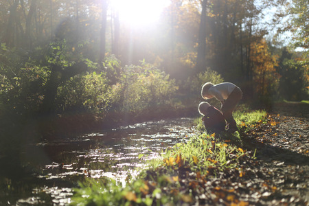 Two young boy children are looking in the water of a small stream as they are exploring outside in the woods on a dirt path.