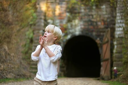 forest railroad: A young boy child is looking around and exploring outside at an old rail road tunnel turned into a bike trail. Stock Photo