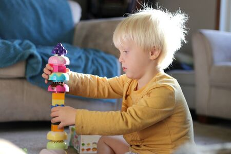 skill: A young 3 year old boy child is sitting at home in the morning sun, stacking and playing with toy building blocks.