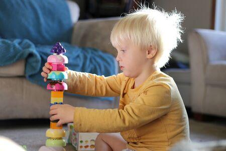 Un joven muchacho de 3 años niño está sentado en casa en el sol de la mañana, apilamiento y juega con los bloques de construcción de juguete. Foto de archivo