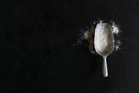 ビンテージ シルバー スプーン スクープは白パン、小麦粉でいっぱい、コピー領域を持つ黒いスレート黒板背景に分離されます。