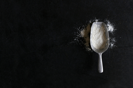 A vintage silver measuring scoop spoon filled with white baking flour is isolated on a black slate chalkboard background with copy-space.