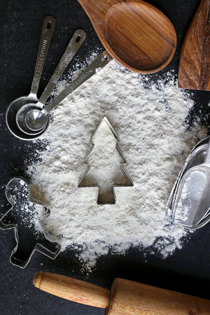 wood cutter: A silver metal Christmas Tree cookie cutter is sitting in a pile of spilled white baking flour, framed by a variety of wood and steel vintage cooking supplies and utensils.