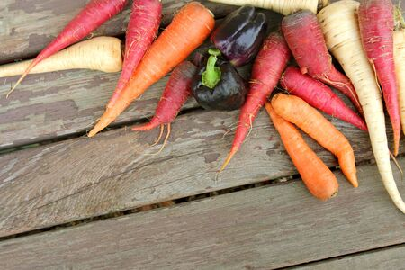 bordering: Organic farm fresh vegetables are bordering a rustic wood picnic table background.