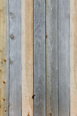 slats: A background of textured rustic wooden plank boards that are knotted and weathered grey and tan brown.