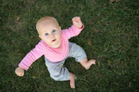 8 9 months: A cute 8 month old baby girl is sitting in the grass looking up at the overhead camera with her amrs in the air.