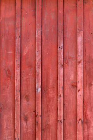 barnwood: The side of an old farm buildings red peeling paint rustic barn-board plank wall background with board and batten siding. Stock Photo