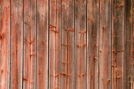 barnwood: The side of an old farm buildings red peeling paint rustic barn-board plank wall background. Stock Photo