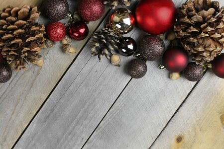 sparkly: Red and gold sparkly christms tree bulb decorations, pine cones, and acorns frame a background of weathered old barn wood. Stock Photo