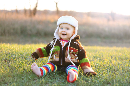 An adorable 8 month old baby girl with bright blue eyes is laughing while bundled up in a winter hat and knit sweater on a cold fall day. Stock Photo
