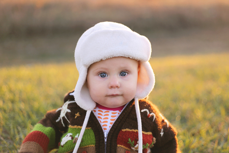 An adorable 8 month old baby girl with bright blue eyes is looikng at the camera while bundled up in a winter hat and knit sweater on a cold fall day.
